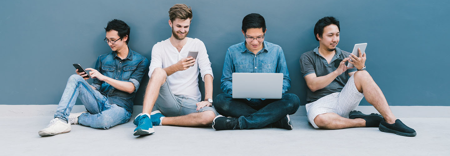 four men using smartphone, laptop computer, digital tablet together with copy space on blue wall