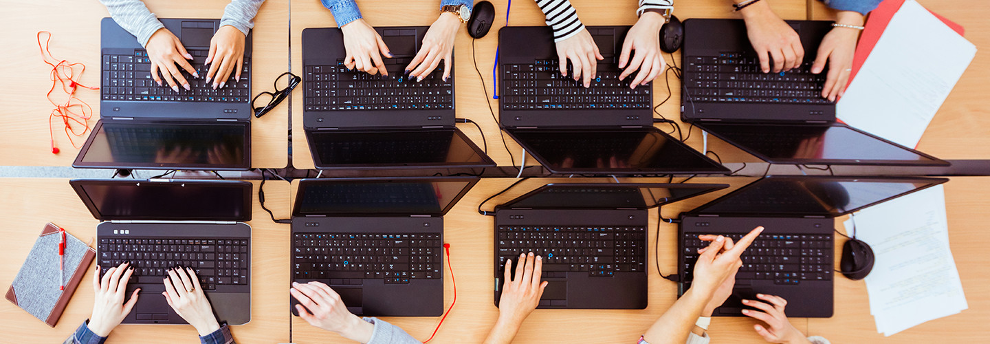 Hands working on computers