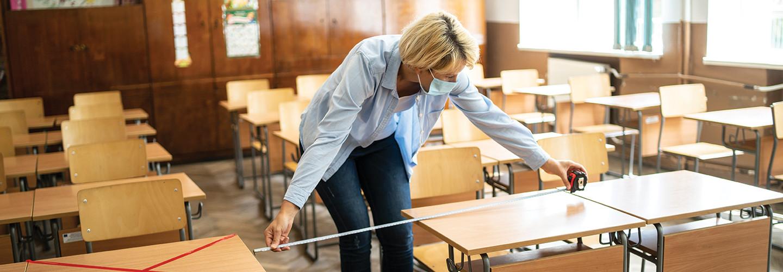 Instructors measures distance between desks