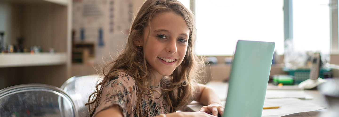 girl remote learning on laptop at home