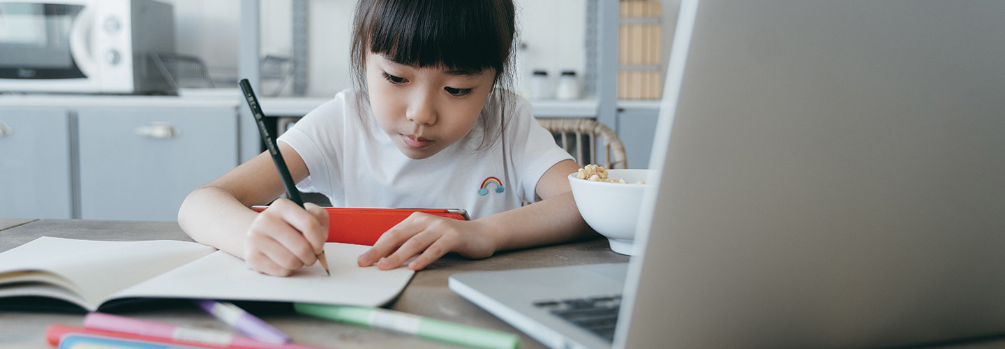 young girl taking notes on paper from computer while holding tablet