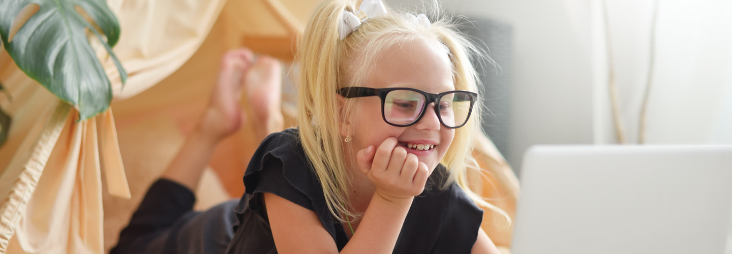 Young female student with black glasses looks happily at a computer screen