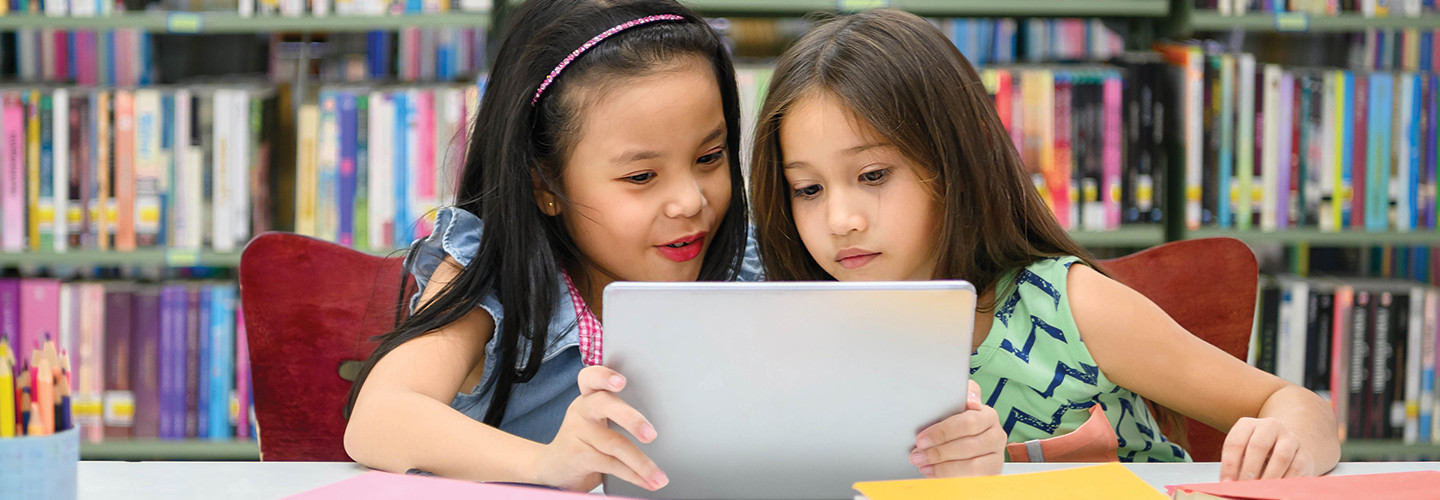 Two girls using tablet for remote learning