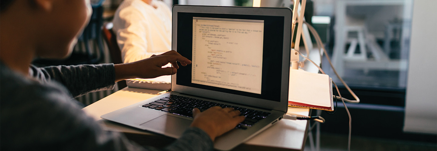 Young student coding on a laptop at home