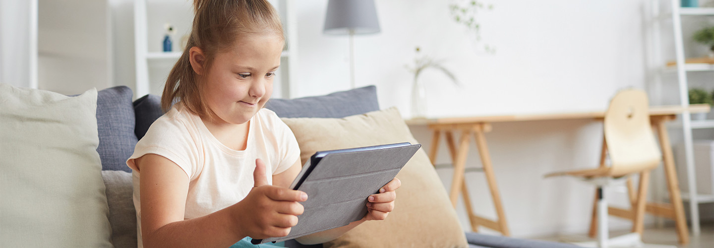young girl with disability using tablet at home