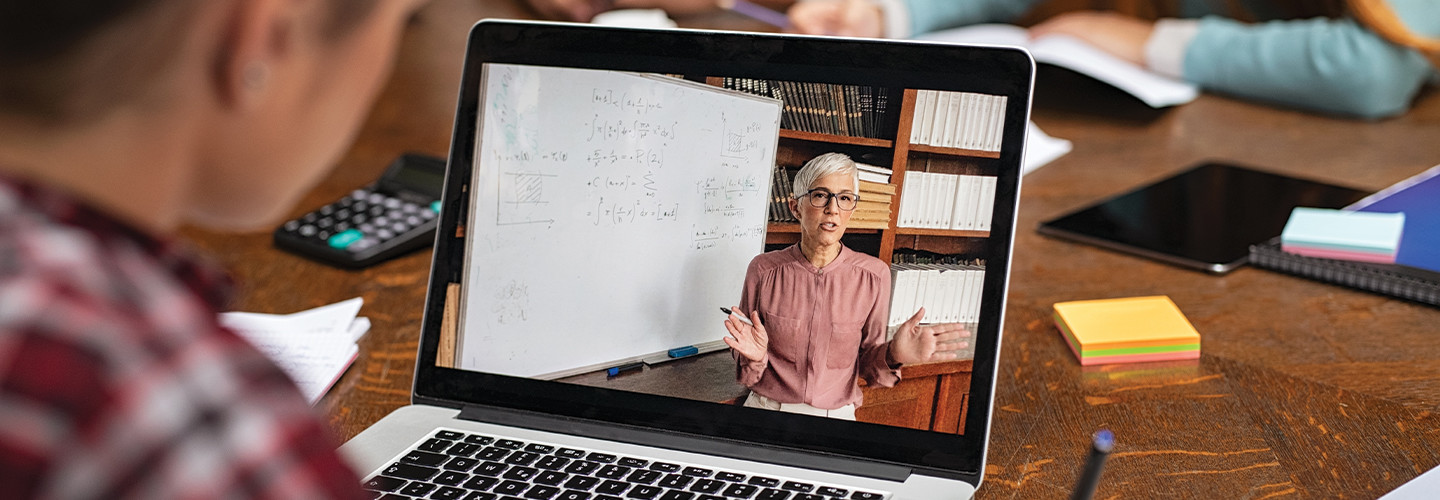 student watches lesson on laptop