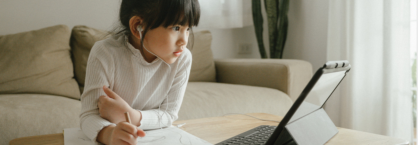 little girl doing schoolwork from home with a digital tablet