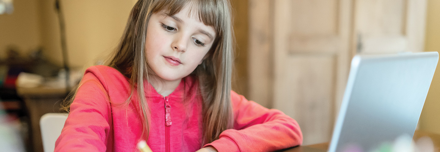 girl taking notes on paper from laptop for school