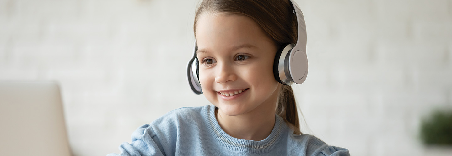 girl with headphones smiling at laptop screen