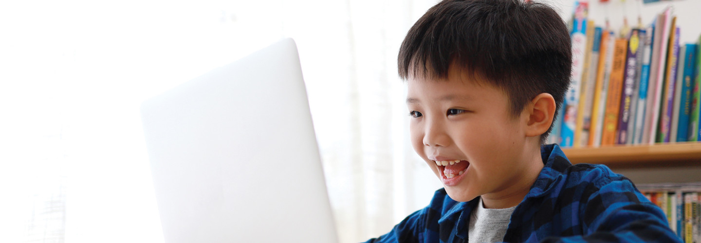 young boy online learning smiling at his computer