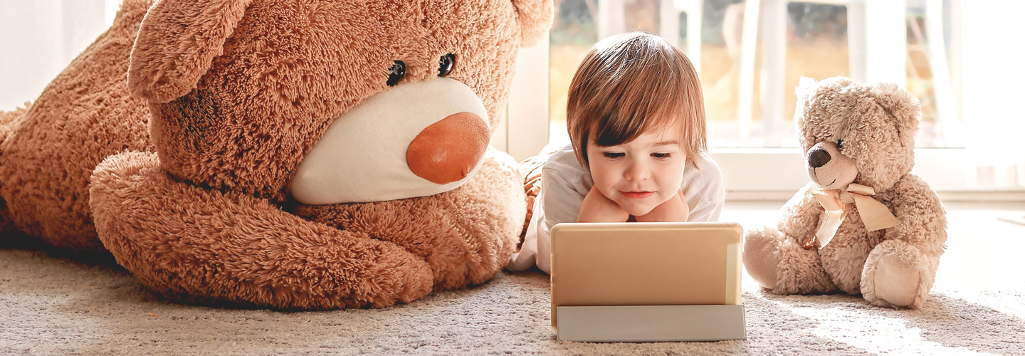 Kindergarten student learns to read on gold tablet with two toy bears