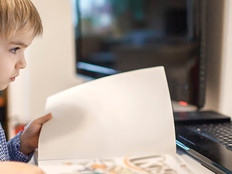 boy opening book while looking at computer screen for school