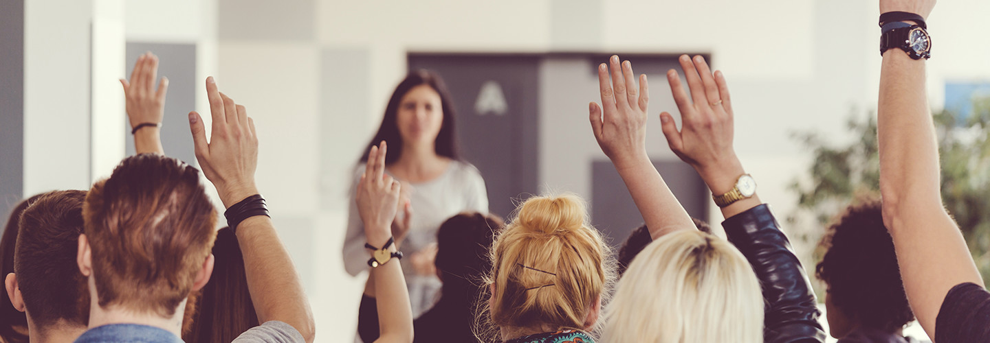 Teachers raising their hands in a training seminar