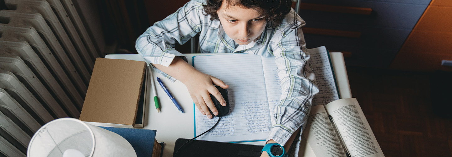 boy using laptop at home for school work