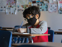 boy with mask in hybrid classroom