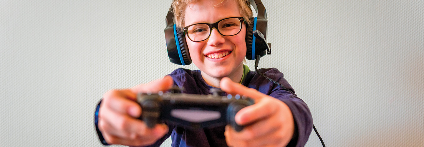 boy with glasses wearing headphones and holding gaming controller