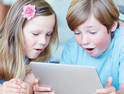 Two kids using a tablet for digital learning