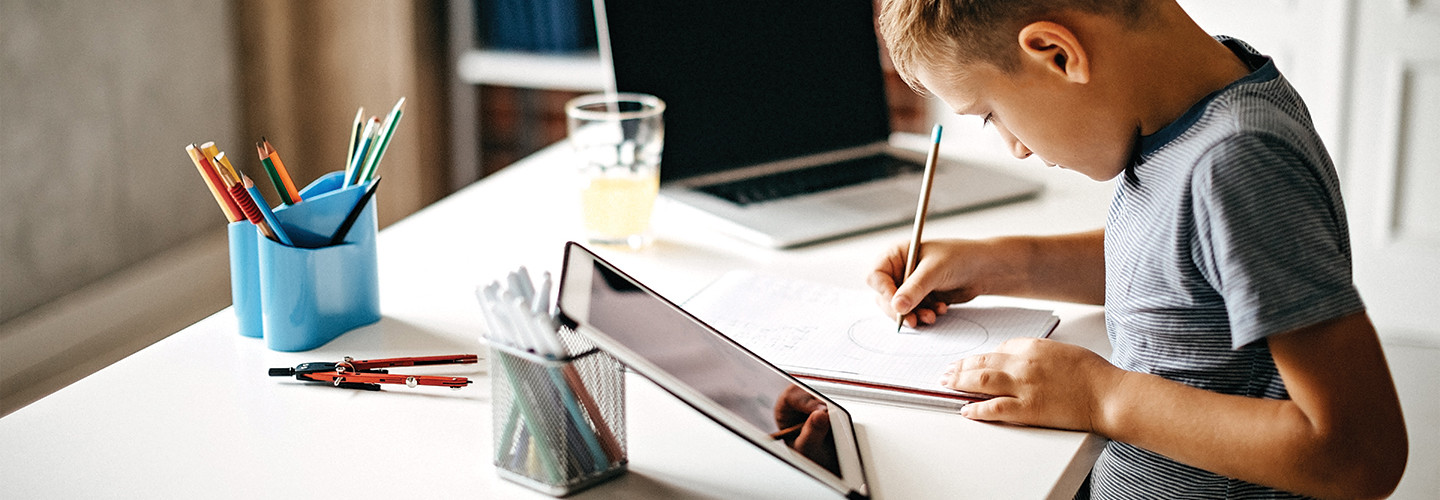 boy using laptop at home for learning