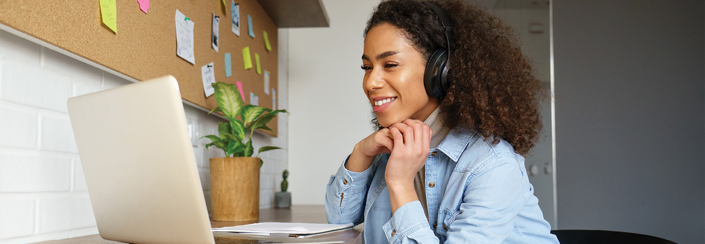 woman with headphones looking at a laptop