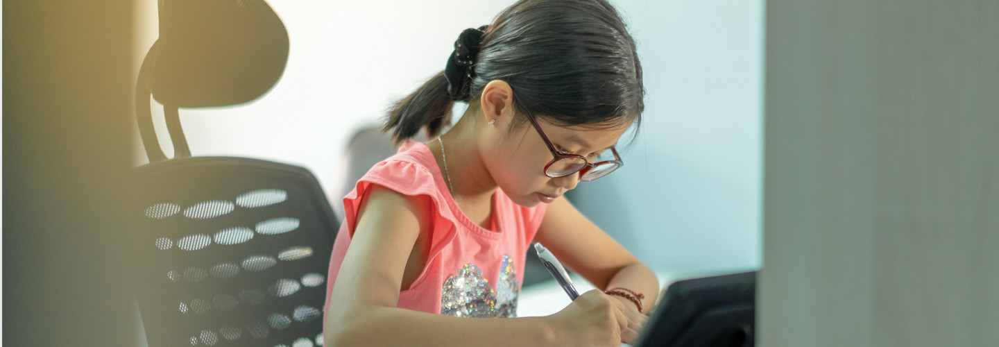 Young girl sitting at desk doing schoolwork