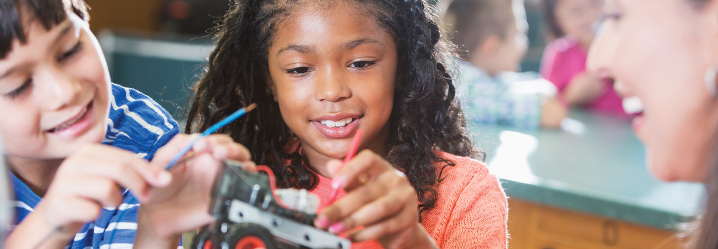 Students engage in STEM lessons with a robotic car while smiling teacher looks on