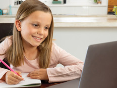 girl smiling and taking notes on paper while looking at computer screen