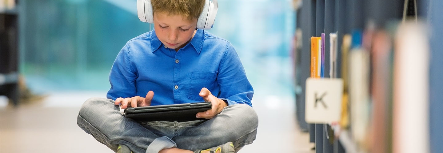 Child on tablet in a library