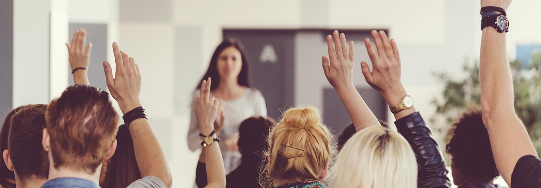 Teachers raising their hands in a training seminar