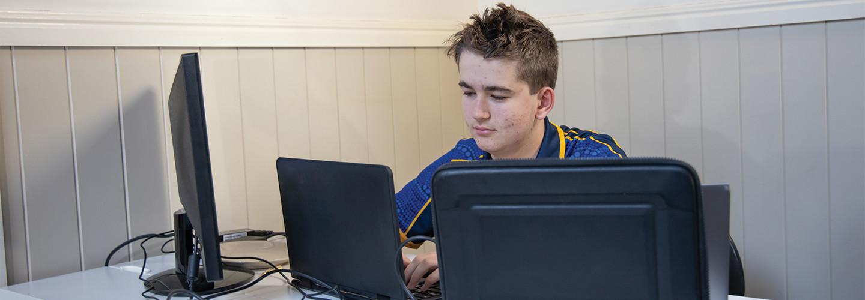 teenage boy using computer at home