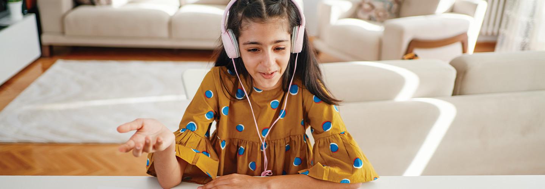 teenage girl with headphones and laptop having online class