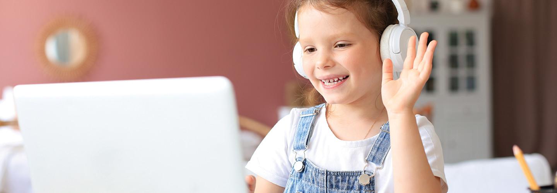 girl in headphones waving at computer screen