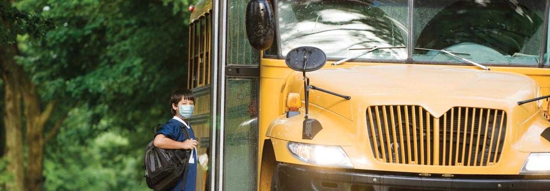 Little boy getting on school bus in a mask