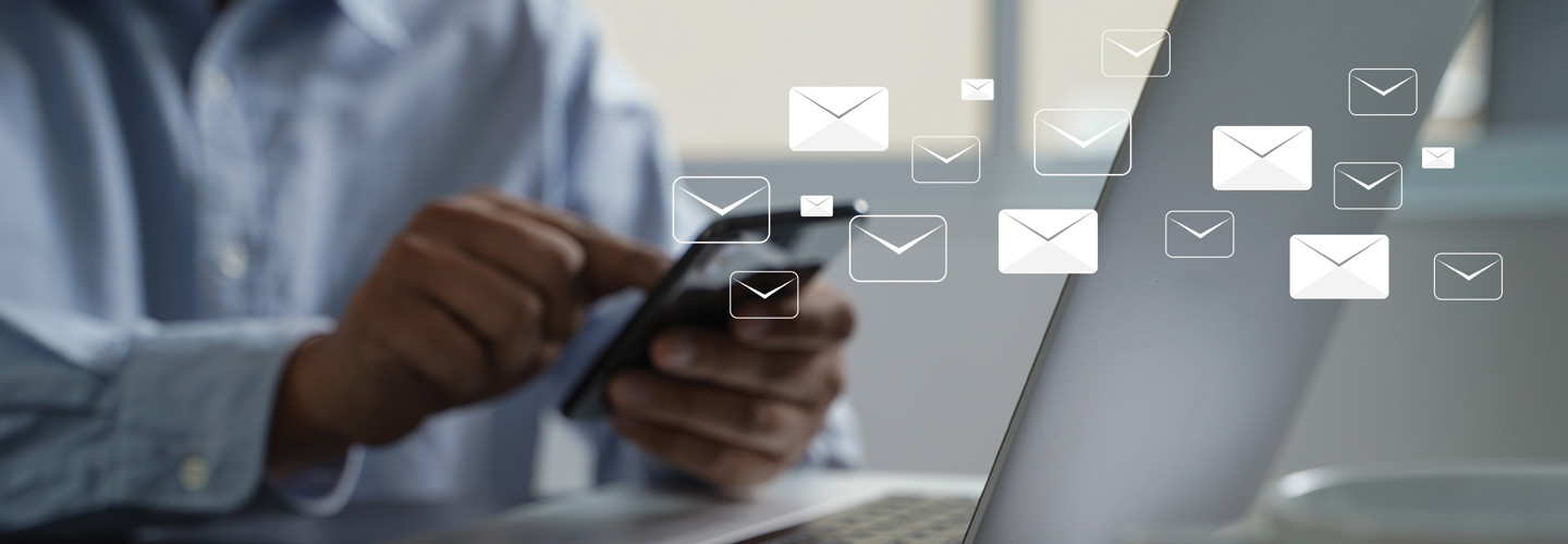 Man on phone and laptop with email icons