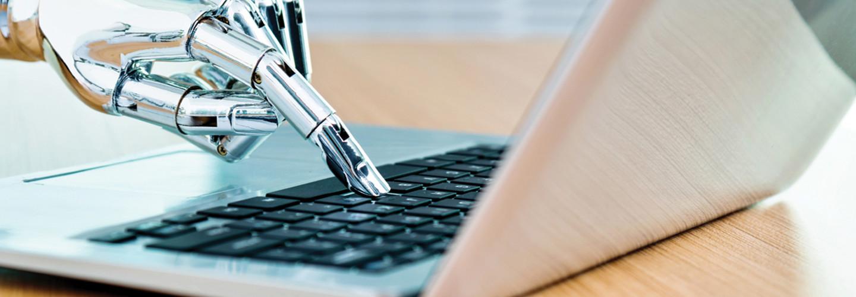 Metallic, robotic hand types on a laptop keyboard - artificial intelligence