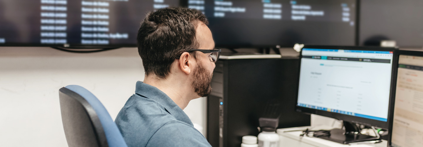 Man sitting in front of computer network monitoring