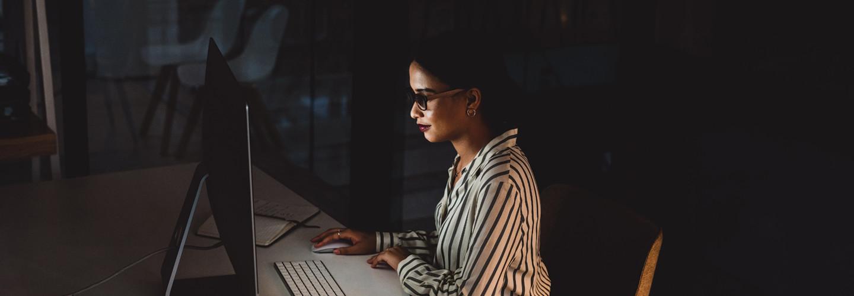 IT leader in front of computer screen in dark room cybersecurity