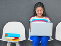 girl in row of chairs on laptop