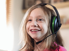 young girl smiling with gaming headset on