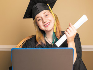 high school girl graduating on her laptop
